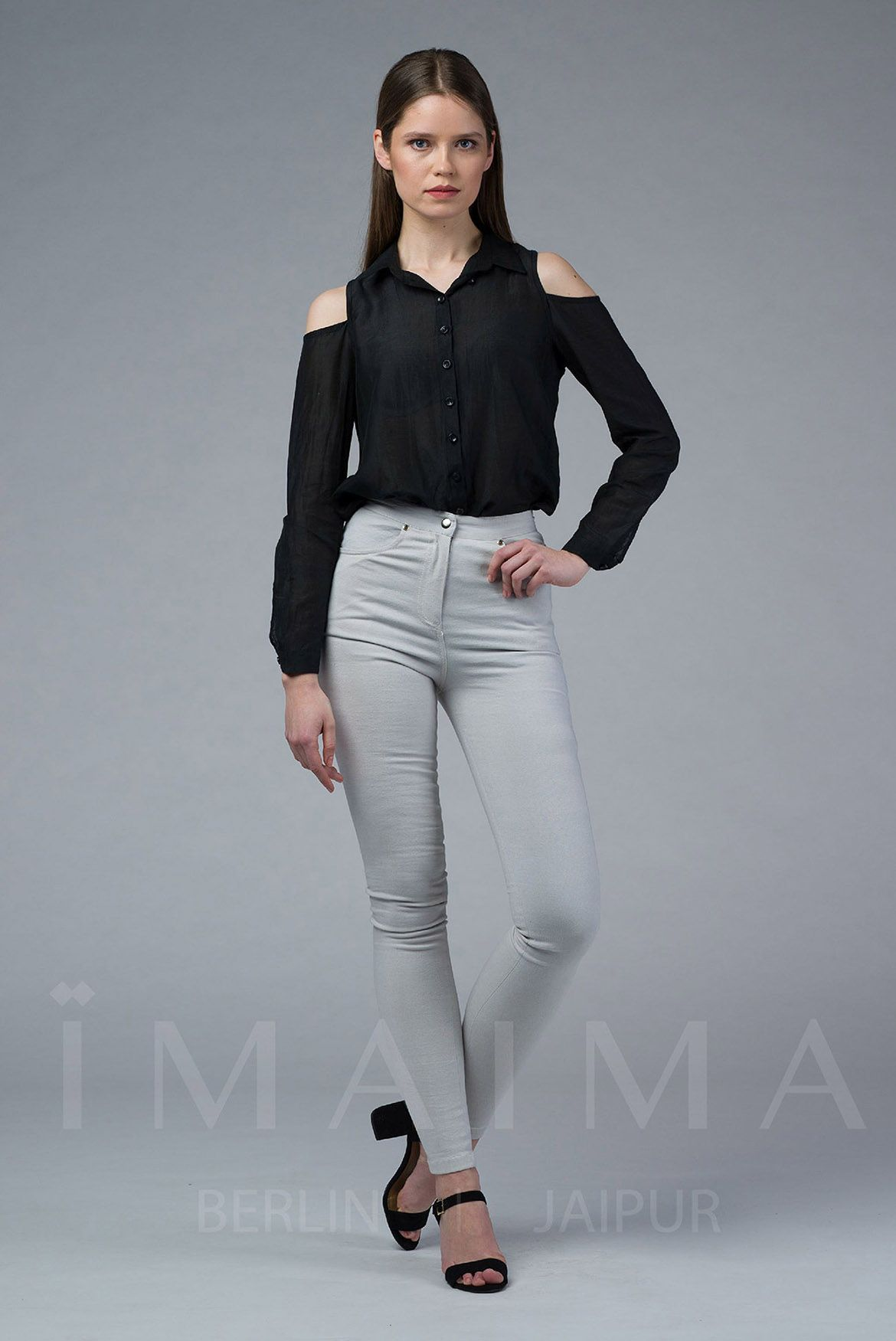 TIARA is an oversize fit silk black blouse with a polo neck and a cold shoulder. With side slits and classic button placket. TIARA has an asymmetric hem which is shorter in the front.
