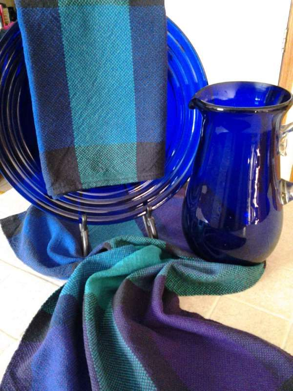 Cricket Loom Stained Glass Towels.  Weave these inspirational towels in plain weave with warp and weft color changes using our Aurora Earth 8/2 100% unmercerized cotton in four richly hued colors.   Each section of color portrays beautiful stained glass windows in deep royal, jade and rich purple surrounded by a black border.   I absolutely loved working with these colors that depict the window pane effects for these towels. These towels are sure to inspire working with color!