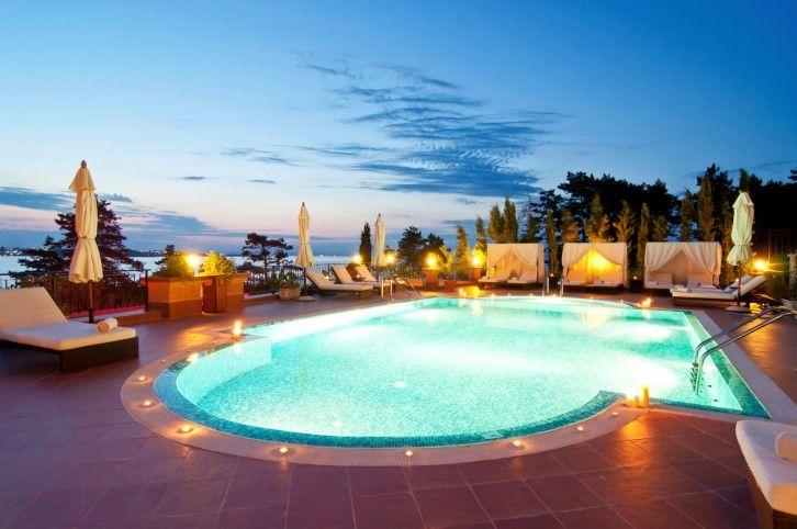 Große ovale Pool bei Nacht beleuchtet mit eingelassenen Innenhof - garten anlegen mit pool