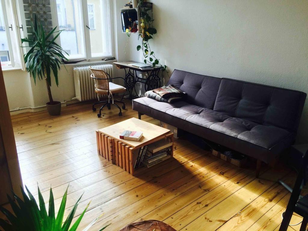 Gemütliches Wohnzimmer mit schönem Holzboden und großen Fenstern ...