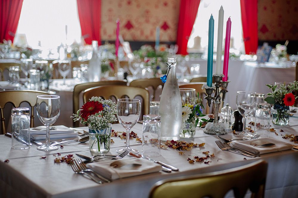 Candelabras with different coloured candles - Image by Jacqui McSweeney Photography - A beaded vintage wedding dress for a brightly coloured quirky wedding in a country pub with origami favours, hat props & bake off desserts