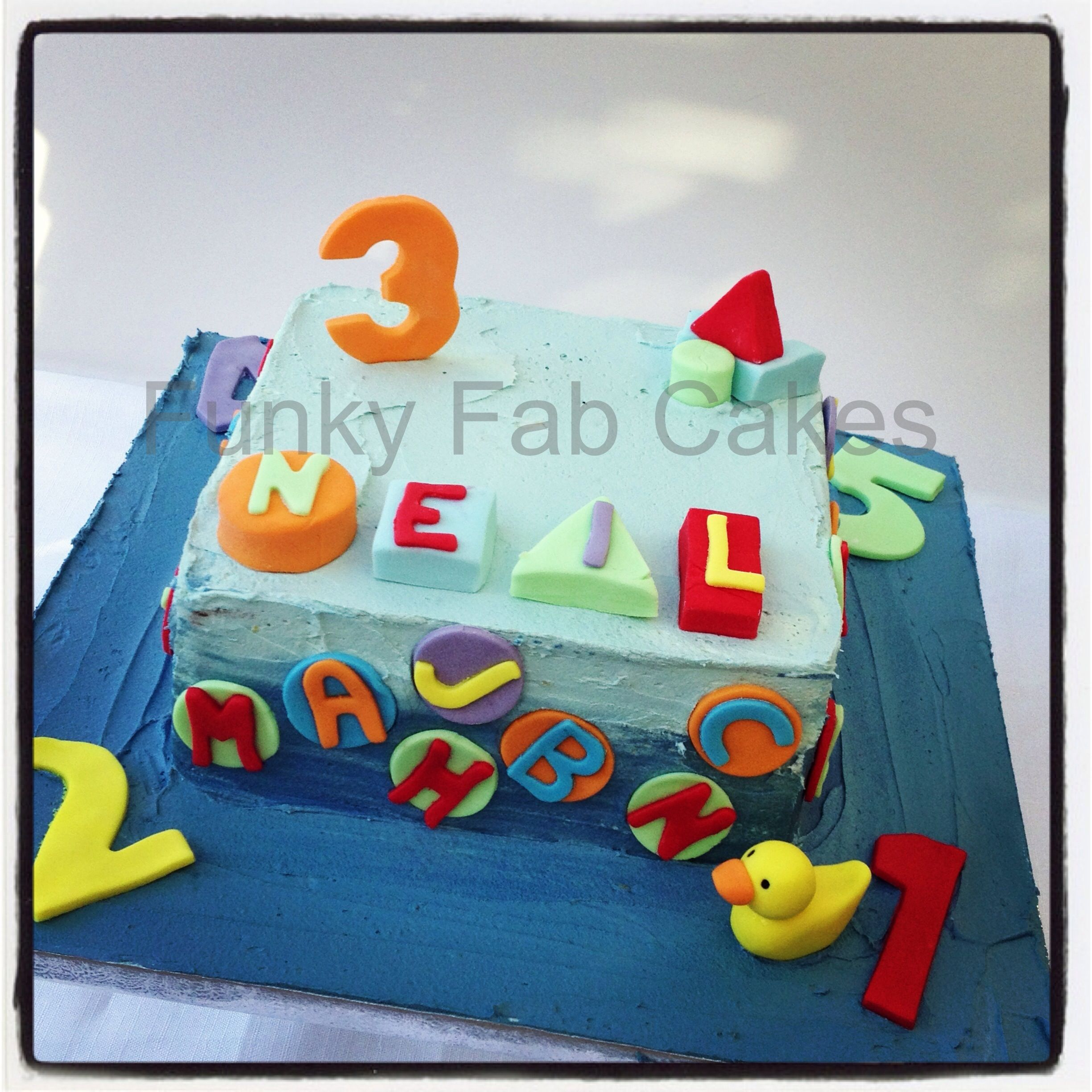 Blue boys buttercream cake with shapes numbers and letters theme