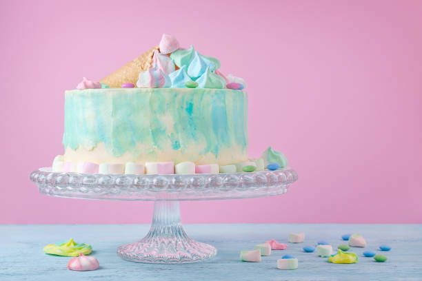 birthday cake in pastel colors marshmallow and candies on pink