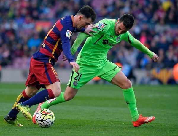 Barcelona's Argentinian forward Lionel Messi (L) vies with Getafe's midfielder Moi Gomez during the Spanish league football match FC Barcelona vs Getafe CF at the Camp Nou stadium in Barcelona on March 12, 2016.