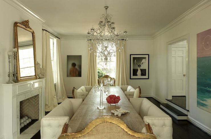 Elegant Dining Room Features Crystal Drops Chandelier Over Long Table Surrounded By White Tufted Benches