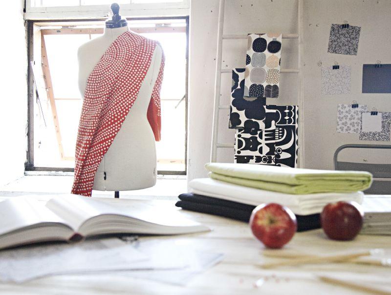 Kankaat taustalla ja mallinuken yllä, Marimekko, 1. krs. Amanda pöytäliinat 100% puuvillaa, 150x250 cm, eri värejä. 24,95 €, Hemtex, 3. krs. Kuviopaperit seinällä, Suomalainen Kirjakauppa, E-taso.
