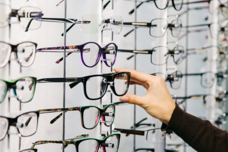 a127a29937 Eyeglasses shop. Stand with glasses in the store of optics. Woman s hand  chooses glasses.