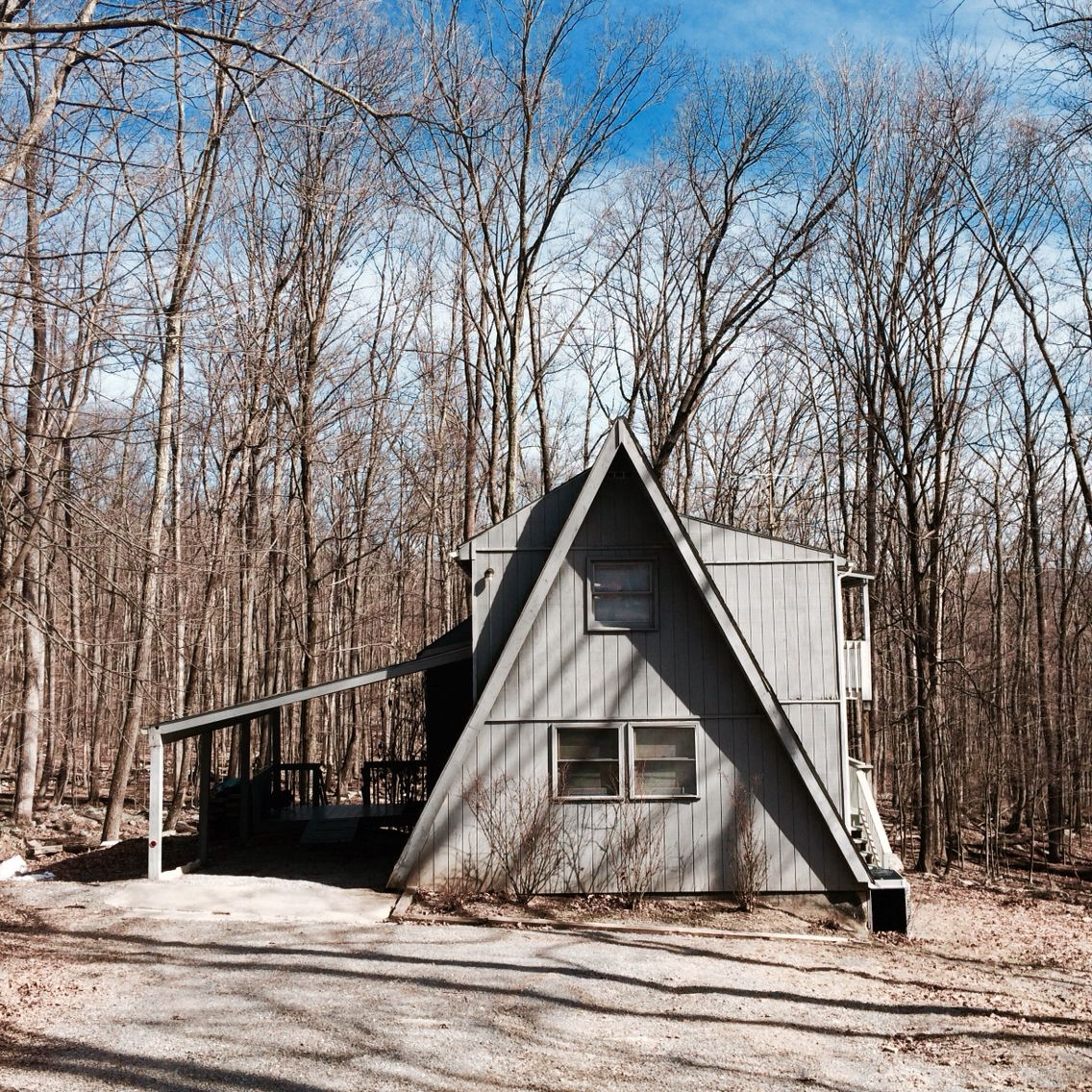 gray a-frame house with car port in berkeley springs, west