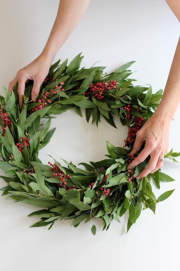 Passez de bonnes fêtes avec nos idées déco de Noël à faire soi-même ! #ideedeconoelafairesoimeme idees deco Noel a faire soi meme couronne porte laurier baies rouges #Noël #christmasdecor #ideedeconoelafairesoimeme