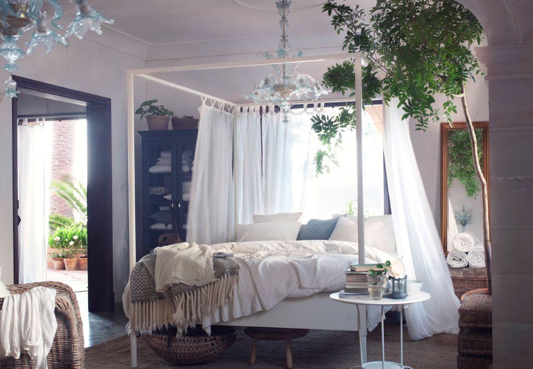 En moderne udgave af en himmelseng omgivet af hvide gardiner og