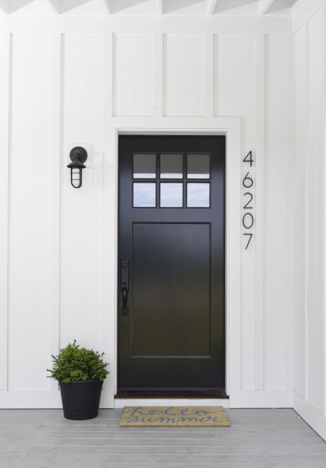 Glossy Black Front Door Contrasting Against White Panels