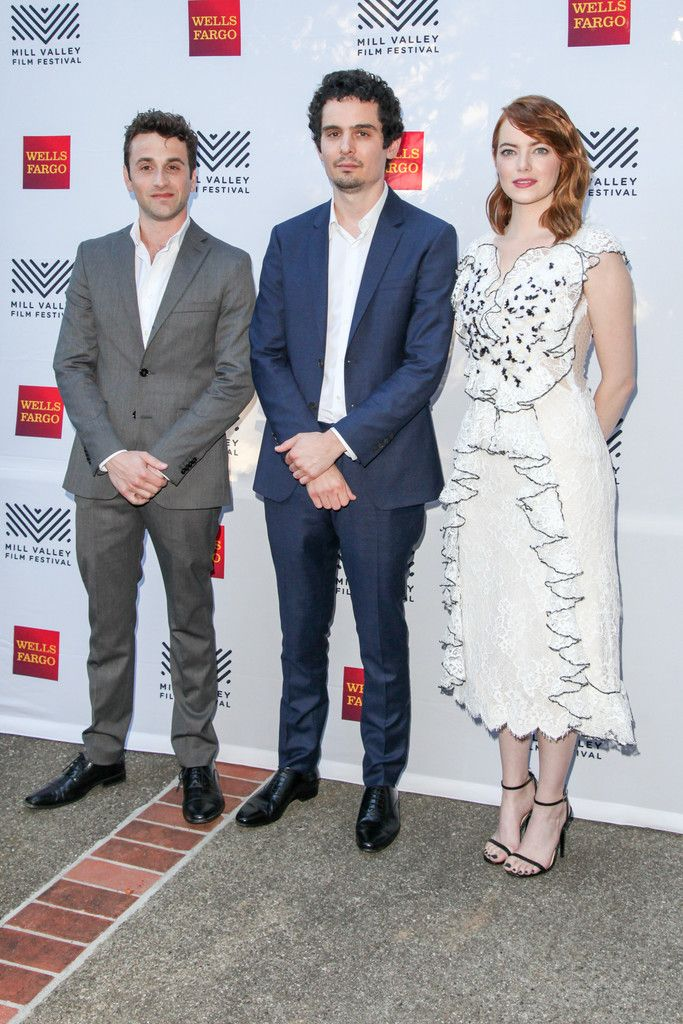 """Emma Stone Photos Photos - """"La La Land"""" composer Justin Hurwitz, director Damien Chazelle, and actress Emma Stone pose for photos on the Mill Valley Film Festival red carpet at The Outdoor Art Club on October 6, 2016 in Mill Valley, California. - 39th Mill Valley Film Festival - Opening Night - 'La La Land' and 'Arrival' - Arrivals"""