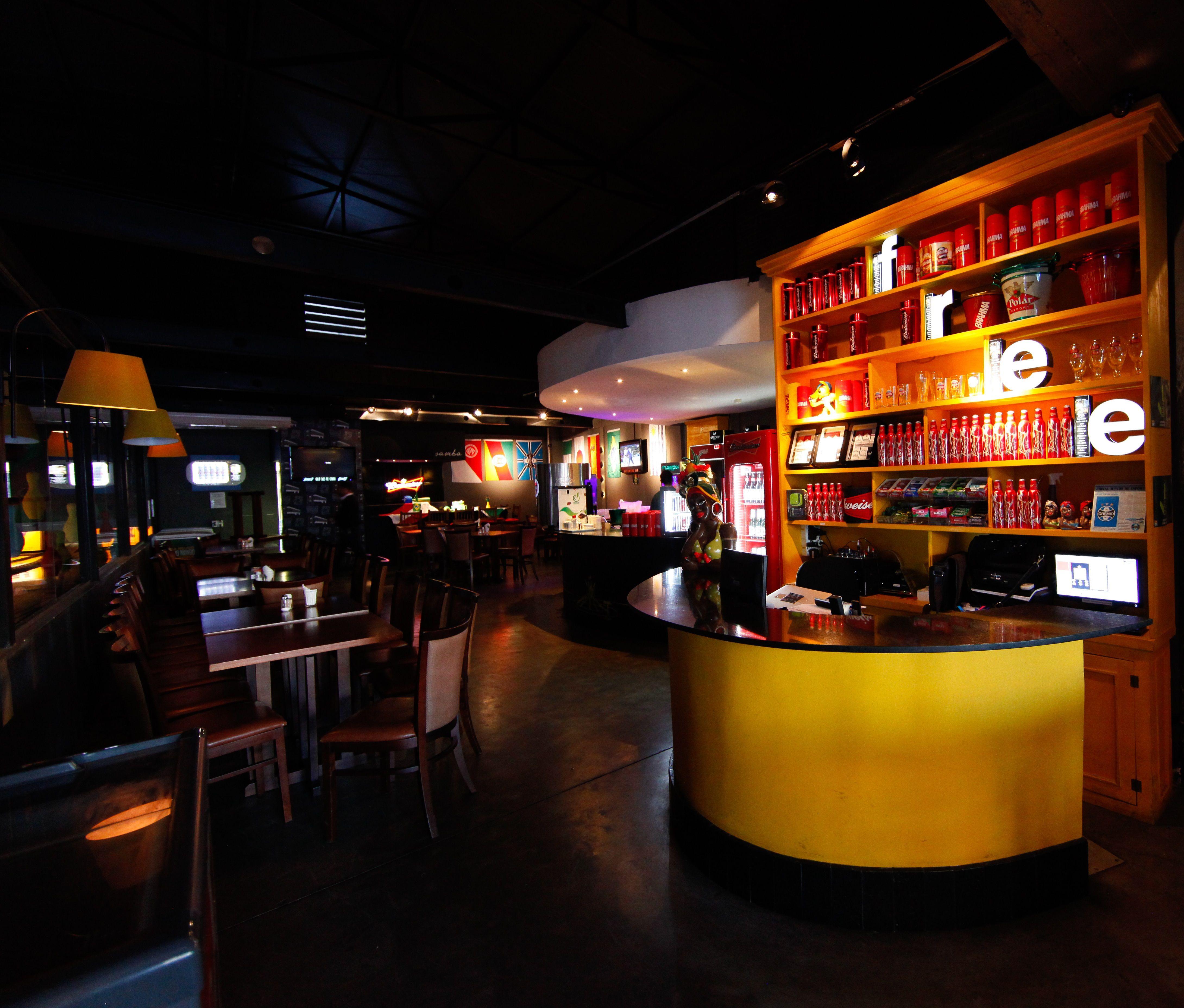 Bar e restaurante na Cidade Baixa/Porto Alegre-RS. Espaço aconchegante para um dos melhores happy hour da cidade, com iluminação intimista, parede, teto e piso em preto com destaque para o caixa em com a bancada circular em amarelo e grande expositor de bebidas.