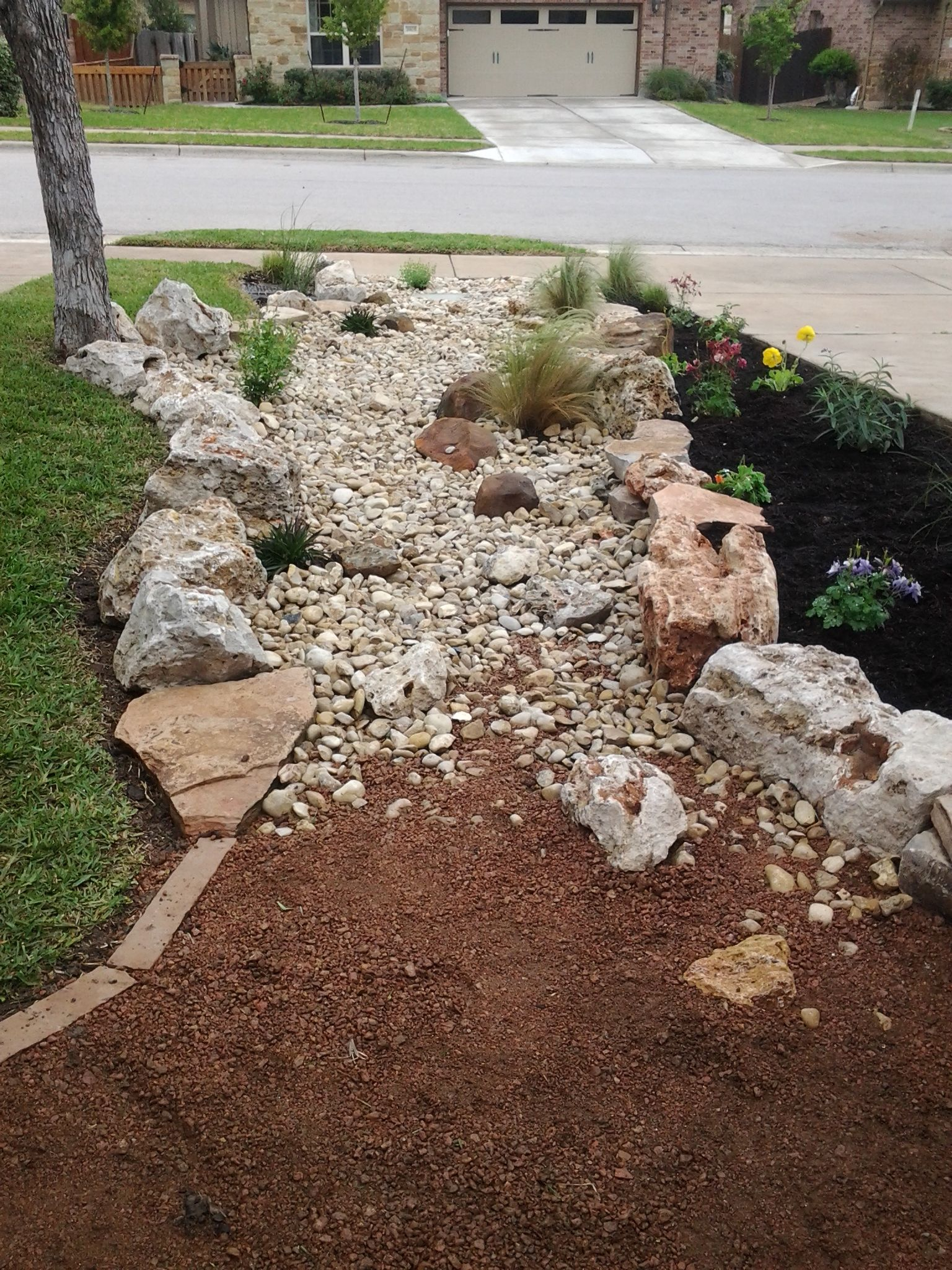 Front yard landscape - dry creek bed using really cool limestone ...