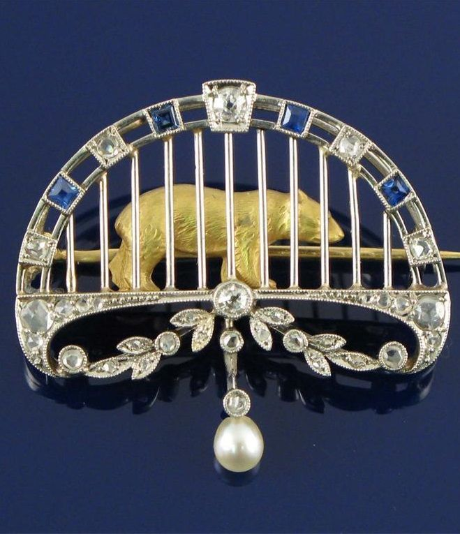 An Edwardian Belle Époque brooch depicting a caged bear, the realistically formed gold bear standing behind a frame of sapphires and diamonds. Suspending a small pearl.