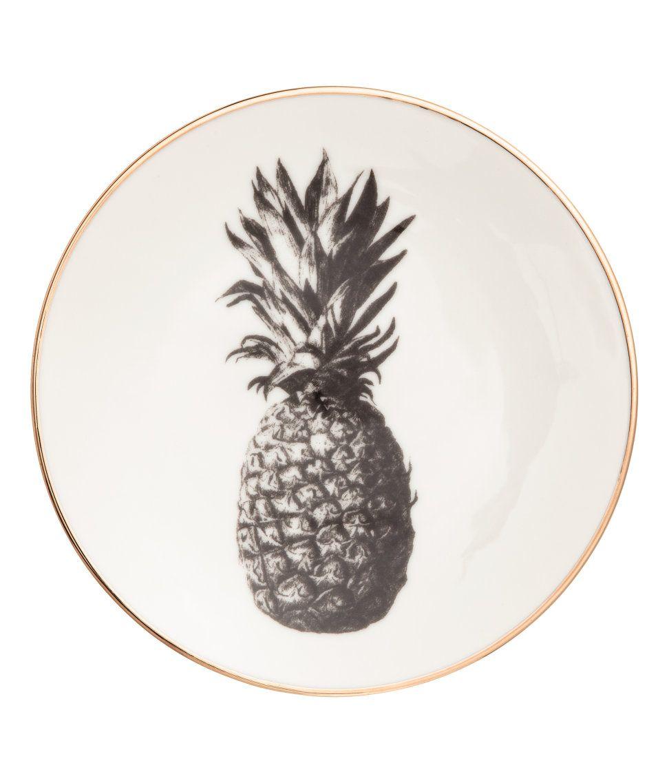 Katso! Pieni posliinilautanen, jossa kullanvärinen reuna ja painettu ananaksen kuva. Halkaisija 15,5 cm. – Käy hm.comissa katsomassa lisää.
