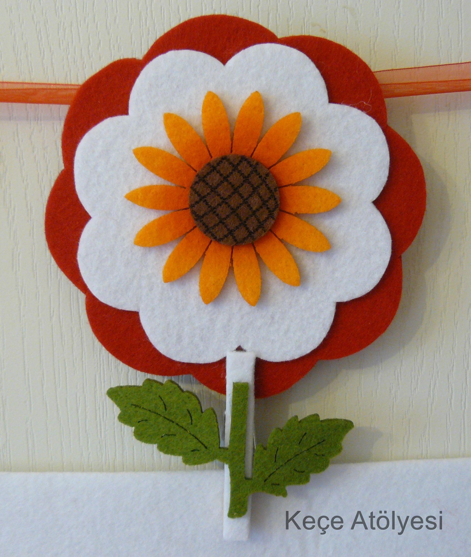 ''Ay Çiçeği'' isimli keçe kapı süsümüz İstediğiniz renk keçe ve kurdeleden yapılır ve sevdiklerinize armağan edilir.  (Turuncu renk çiçek ve yeşil yaprak değiştirilmez)  Keçe Atölyesi yazan kısma istediğiniz renk yün top keçeden isim yazılır.