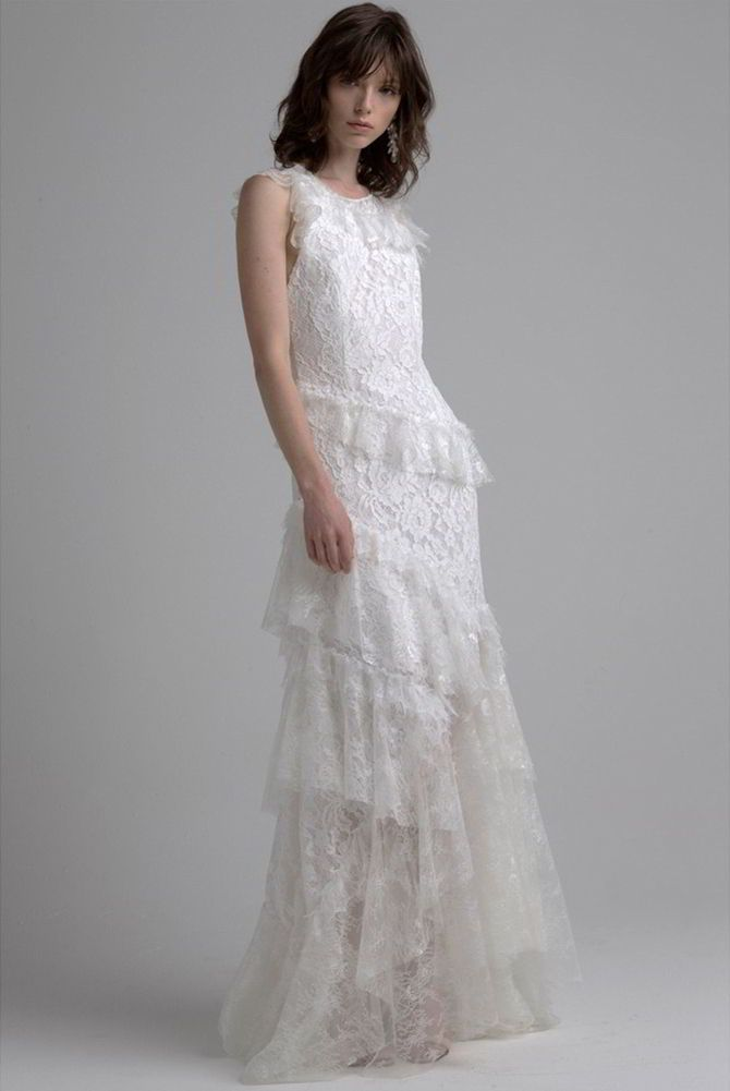 Sleeveless mixed lace gown with asymmetric tiered ruffles and sheer back.