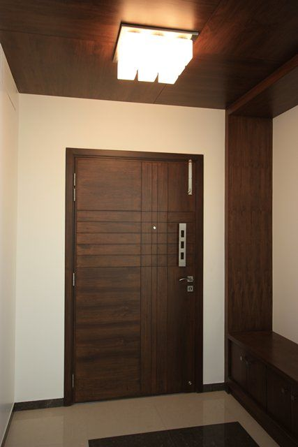 Foyer in the entrance gives a warm look in wooden false for Foyer design ideas india