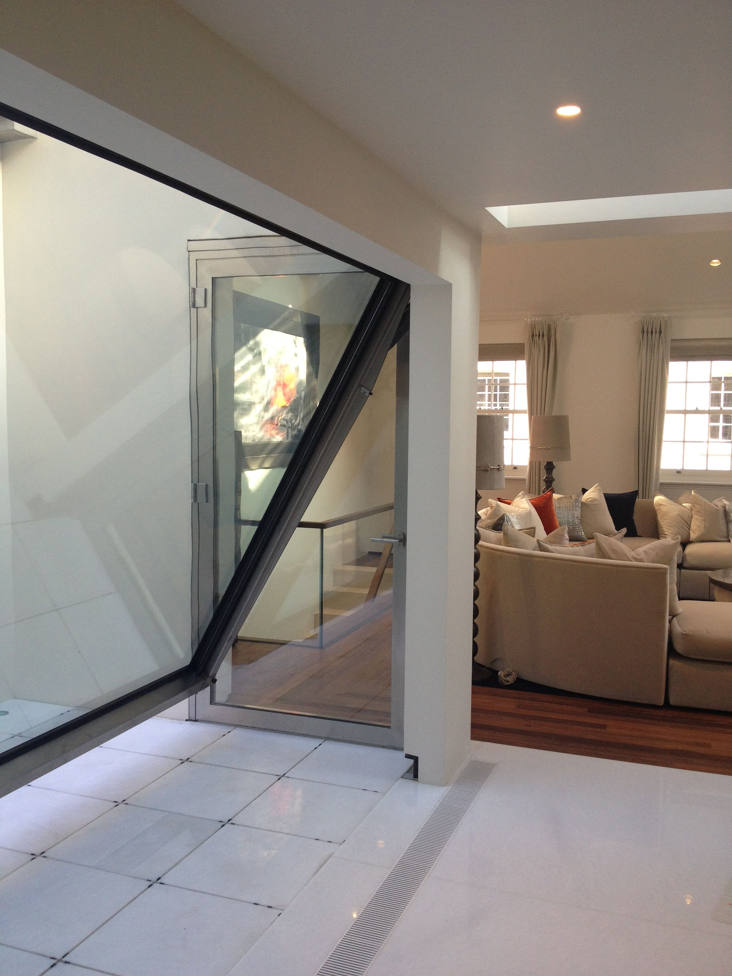 Large hinged glass wall creating a sheltered patio area in a small ...