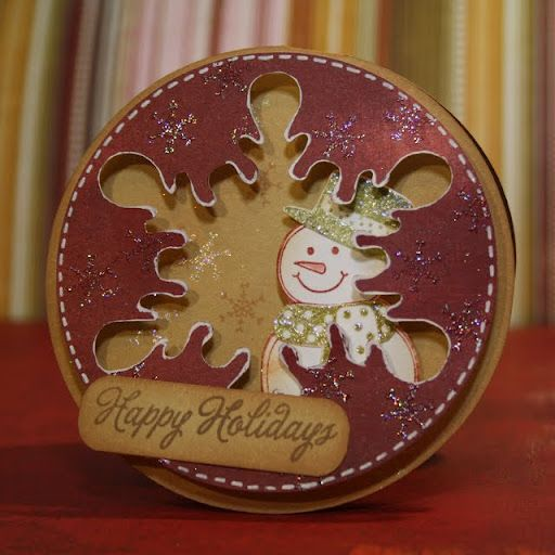 Snowman in behind a big round snowflake.  Nice card!
