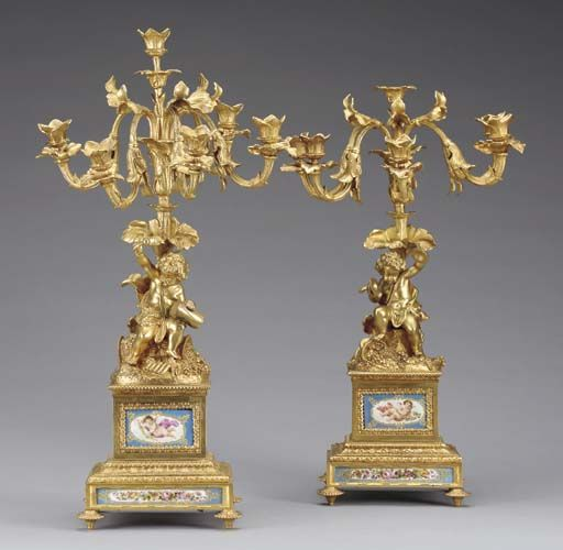 A pair of French Sevres-style porcelain-mounted ormolu six light candelabra, Circa 1890,  Each with a putto sat beside a spilling basket of grapes, the leaf-cast central stem issuing five scrolled candelarms, the base set with turquoise-ground plaques depicting flowers and putti. Christie's.