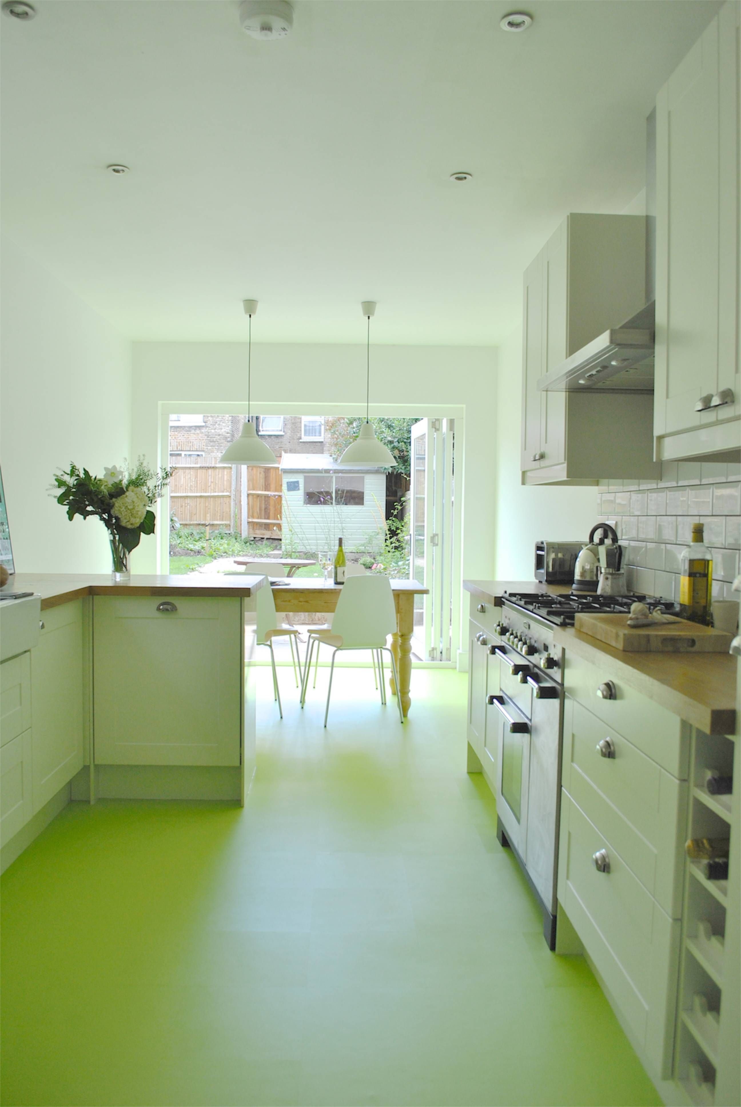 Green kitchen design with tan wooden countertop and white