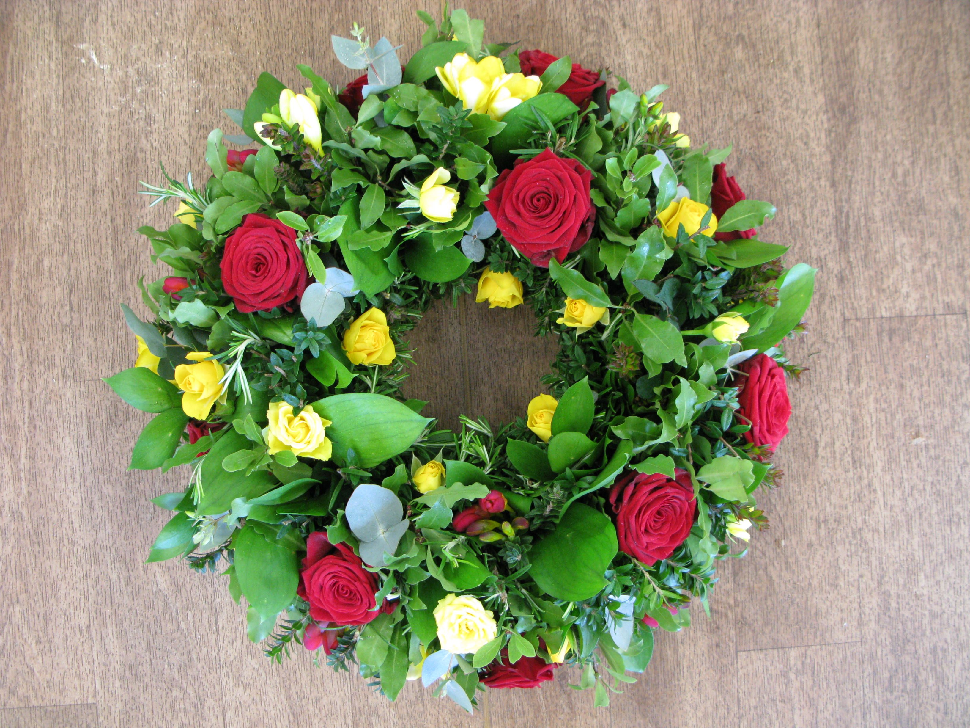 A traditional wreath of roses and freesia funeral flowers a traditional wreath of roses and freesia izmirmasajfo Images