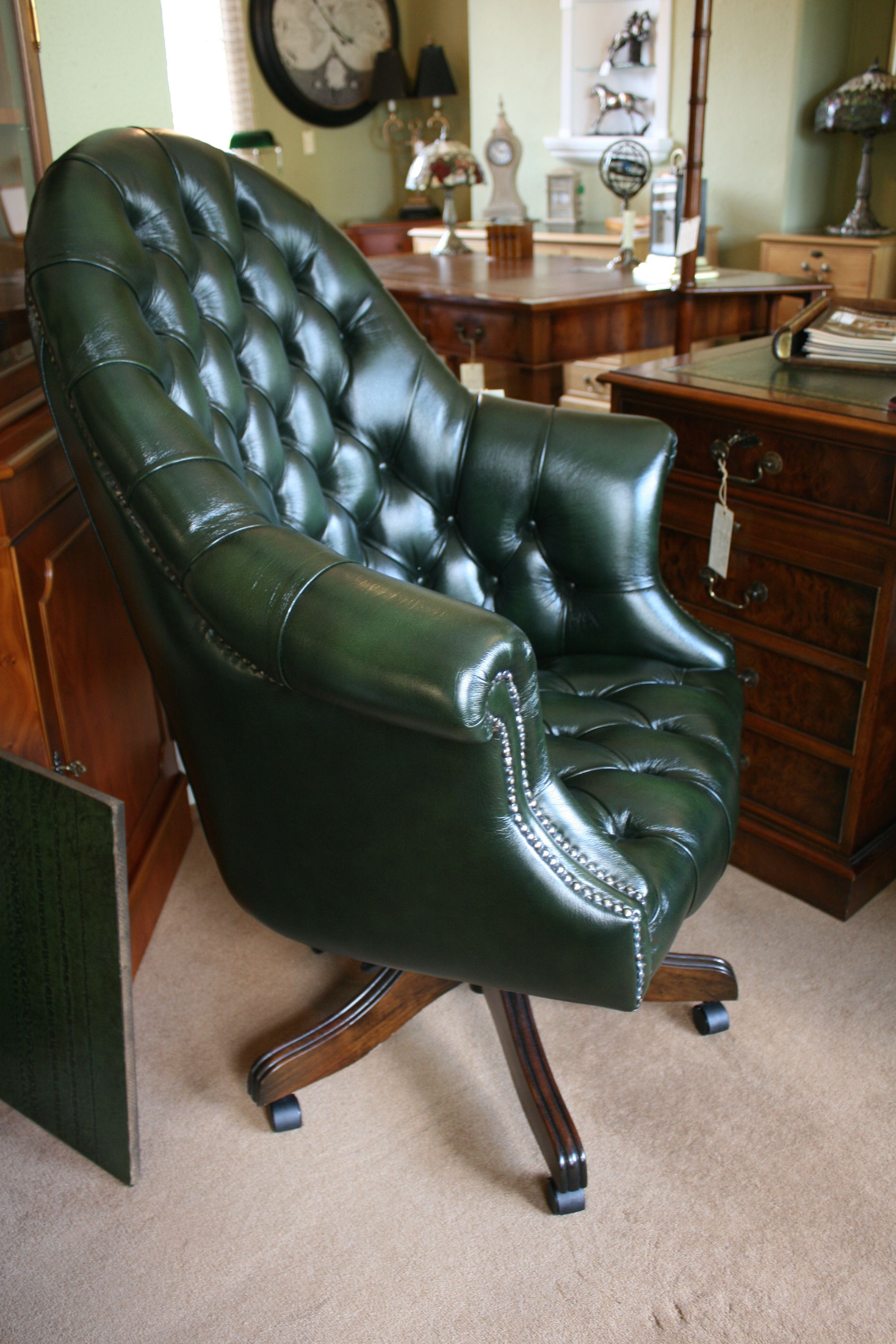 A bottle green leather directors swivel chair buttoned