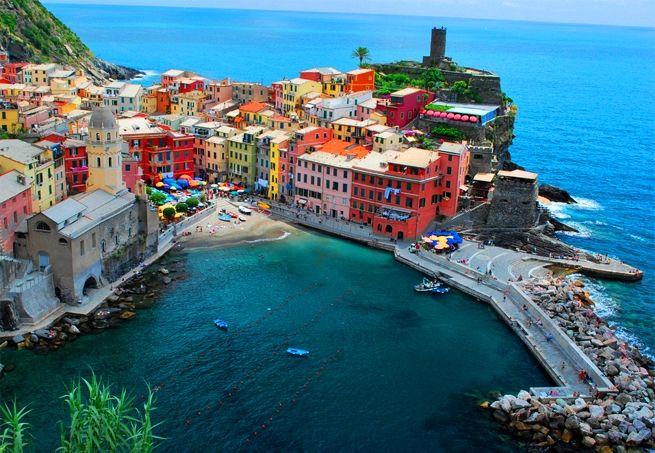 Cinque Terre - Itália. Os prédios de cores fortes se aglomeram nesta região, que fica à beira do Mediterrâneo. A região de Cinque Terre é um dos maiores atrativos turísticos em Riviera Ligure, na região de La Spezia, ao sul de Milão. O trecho de terra é considerado um patrimônio mundial da humanidade pela UNESCO desde 1997.