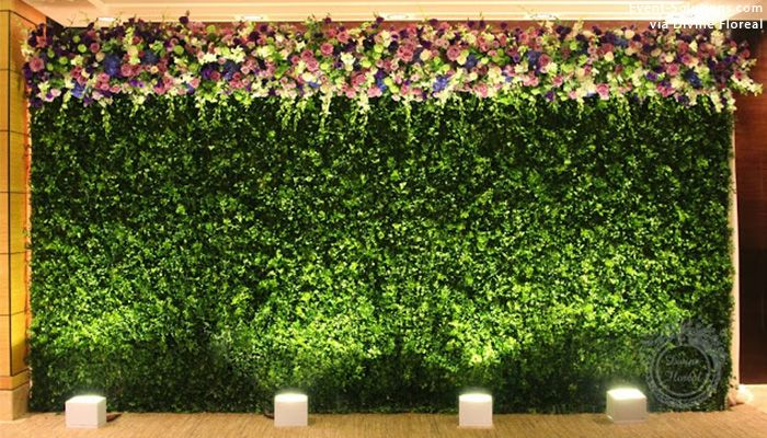 A Greenery Wall With Floral Accents Modern Wedding Decor