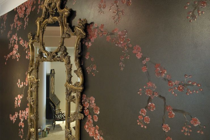 This accent wall in a lobby entrance has a base coat of Smoke metallic paint by Modern Masters and then a cherry blossom tree branches cascade down on top of the metallic finish.