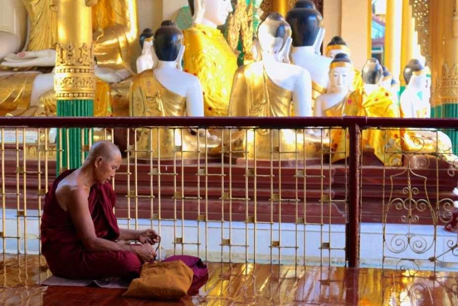 Monk in prayer at Shwedagon Pagoda, Yangon
