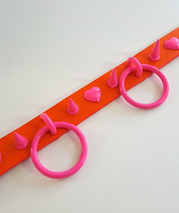 Handmade Neon Orange Genuine Leather choker with NEON Pink powder coated hardware and hearts. The strap and hardware are black light reactive <3 The O-Rings are 1.5 inches. The leather is 1 inch wide.  Fits 12.5-16.5 inch necks.  This is a ready to ship collar. Please allow me 3-5 days to ship it out.  If you have any questions please contact me!  Follow my Instagram @tumorcrunch for new items, shop updates, discounts, and giveaways