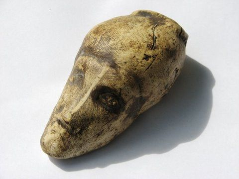 """This is a """"portrait"""" of a woman found in Dolní Věstonice, south of Brno, Czech Republic. Possibly the oldest known replica of a human head, it was carved from a mammoth tusk. The woman has an """"awry,"""" or deformed, face. The skeleton of a woman with just such a face, having traces of a long jaw joint inflammation, was also found at Dolní. The grave and its contents indicated a very prominent or powerful person, so there's much speculation that it's the same person, possibly a shaman or mystic."""