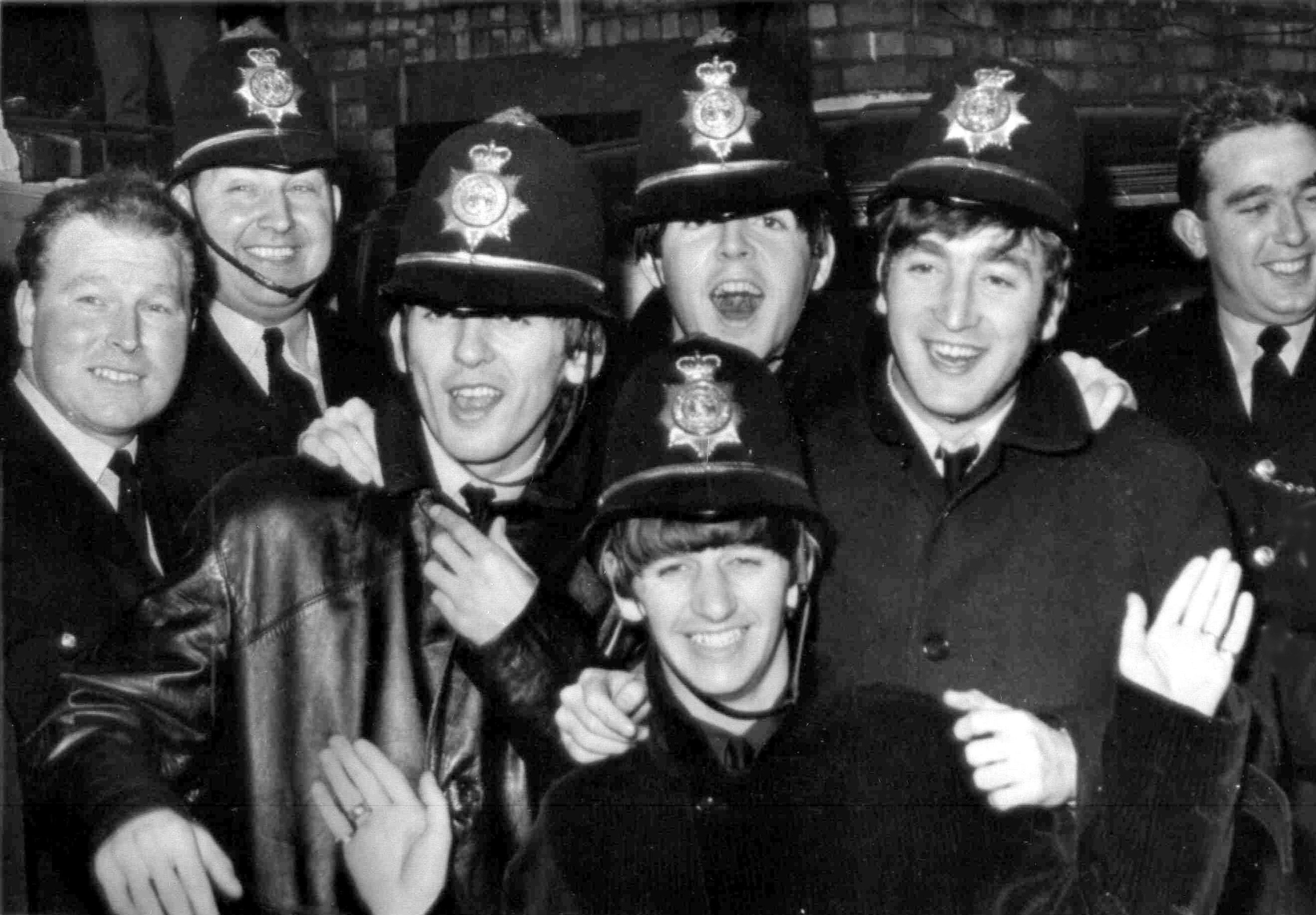 The Beatles arrived almost unnoticed at the Hippodrome, Birmingham, Nov. 10, 1963, dressed as policemen. They are George Harrison, third left, Paul McCartney, John Lennon and Ringo Starr in front. Others in picture are real policemen. (AP Photo)