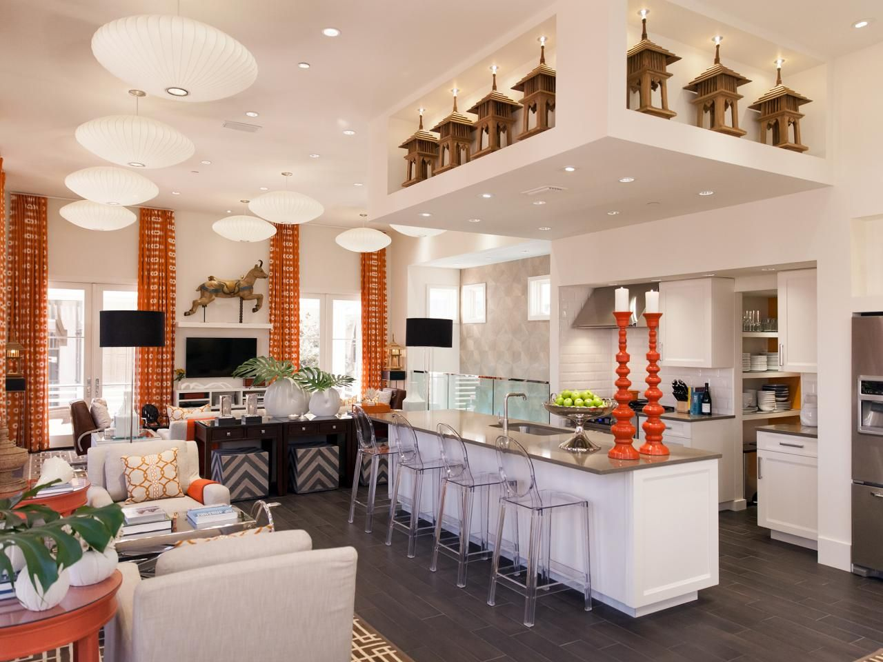 This striking white kitchen, as seen on HGTV's Live In Vern's House, features an open-plan kitchen that connects to the living area. Vibrant orange accents and flea-market finds, as well as international and Asian-inspired elements, help fill the space with visual interest and a playfully contemporary vibe.