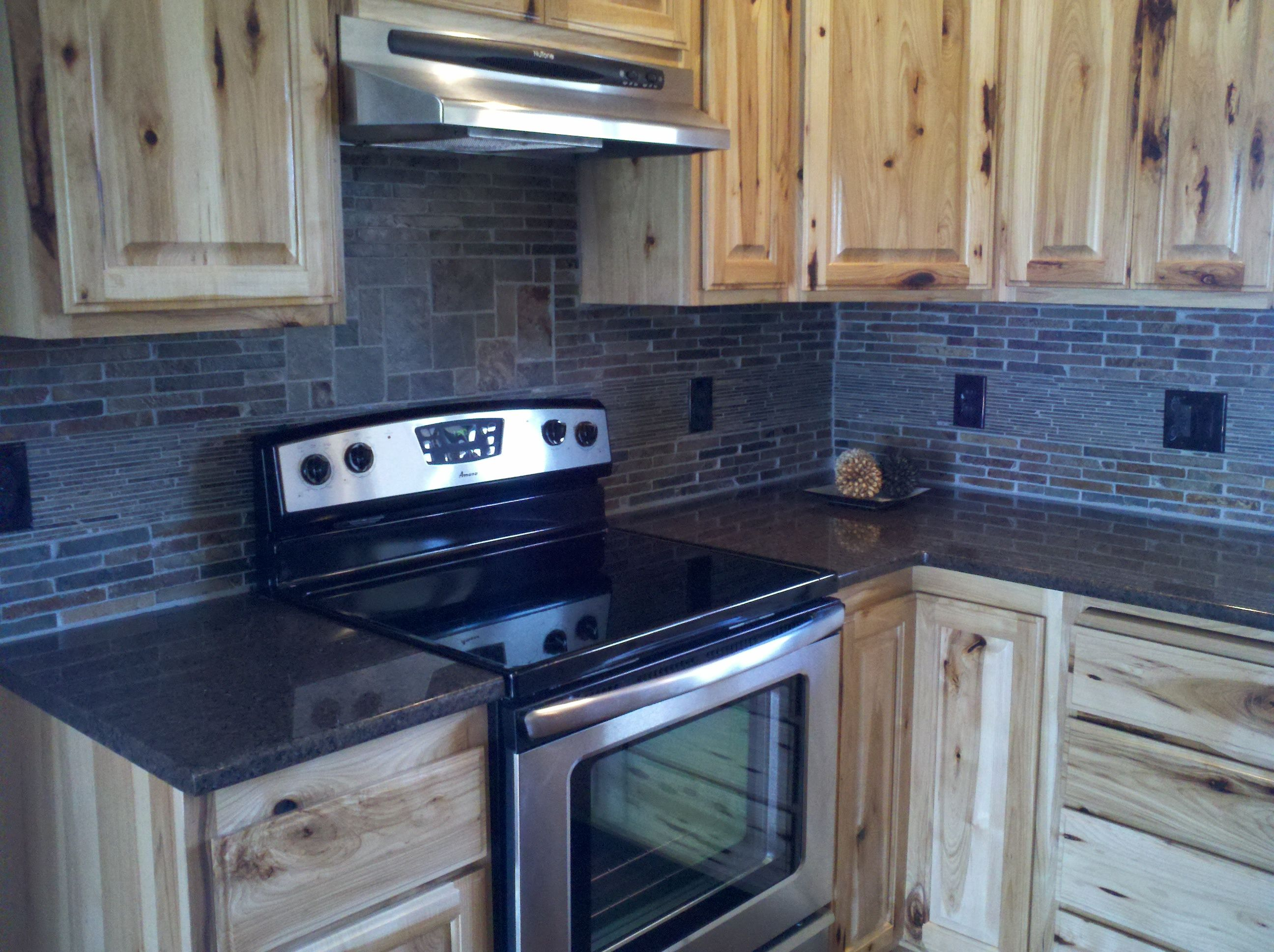 Natural stone backsplash with Layered tile. Custom hickory cabinets ...