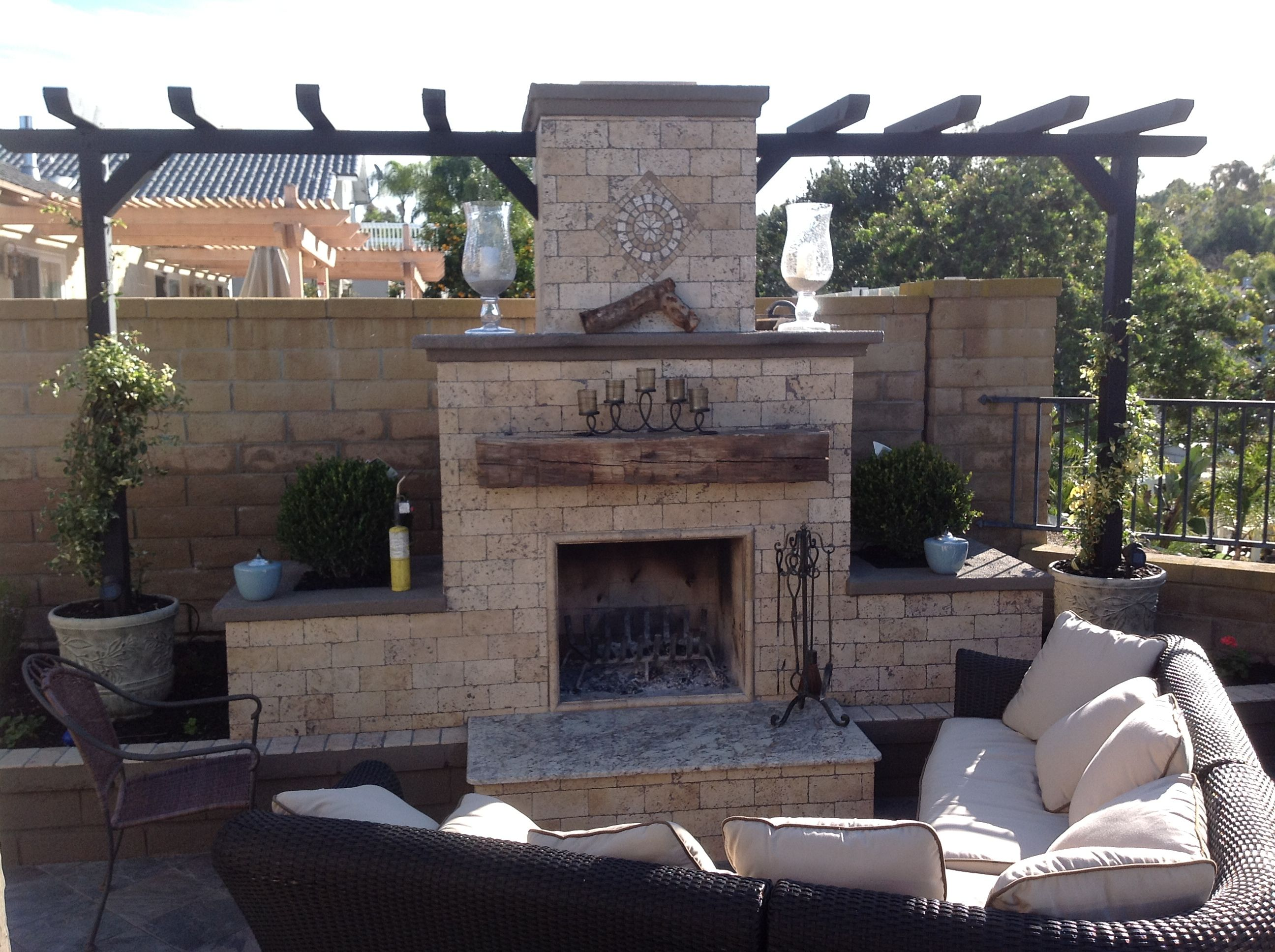 travertine veneered diy fireplace built using a backyard flare