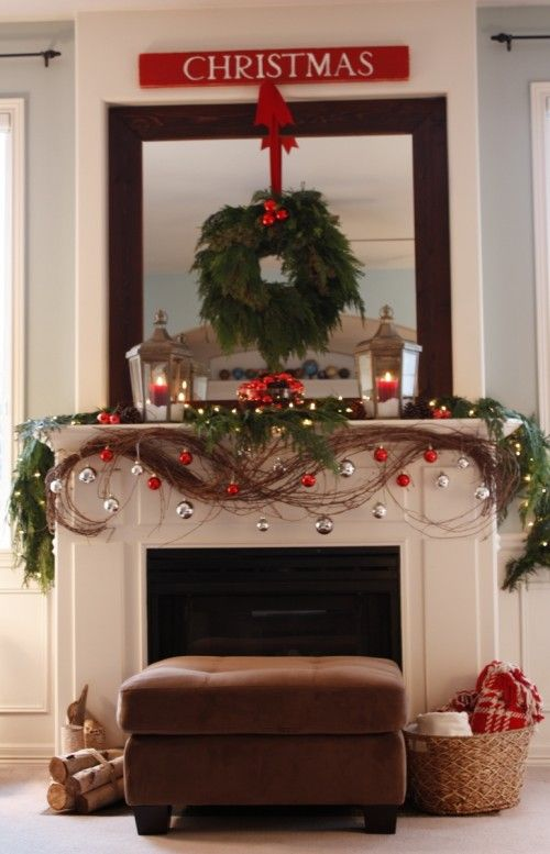 Christmas decorated mantel. Love the grapevine with shiny balls hanging from it. I would add more cedar branches and lights. The wreath needs a bigger bow.