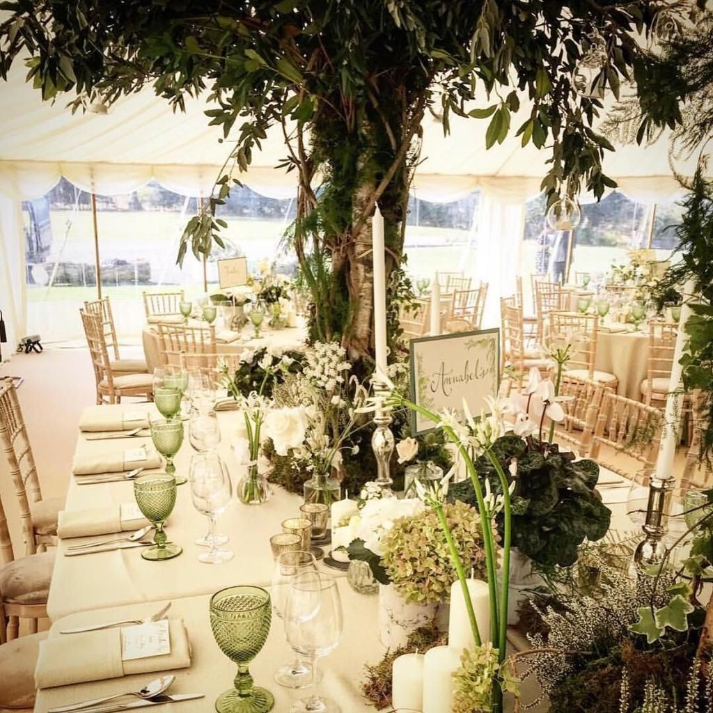 Statement Top Table Design Using Oversized Tree Arrangements With Low Level Eclectic Styling Using Candlesticks City Flowers Reception Table Table Decorations