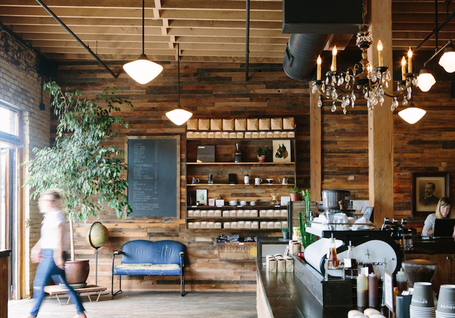 Warm Distressed Wood Surrounds This Rustic Coffee Shop Modern Pendant Lightings And Dainty Chandelier Add A Touch Of Glamour To The Cafe