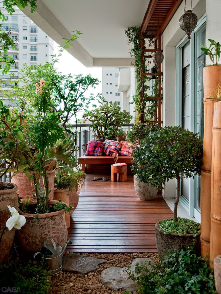 Osez les lattes de bois et cailloux pour décorer le sol de votre balcon.
