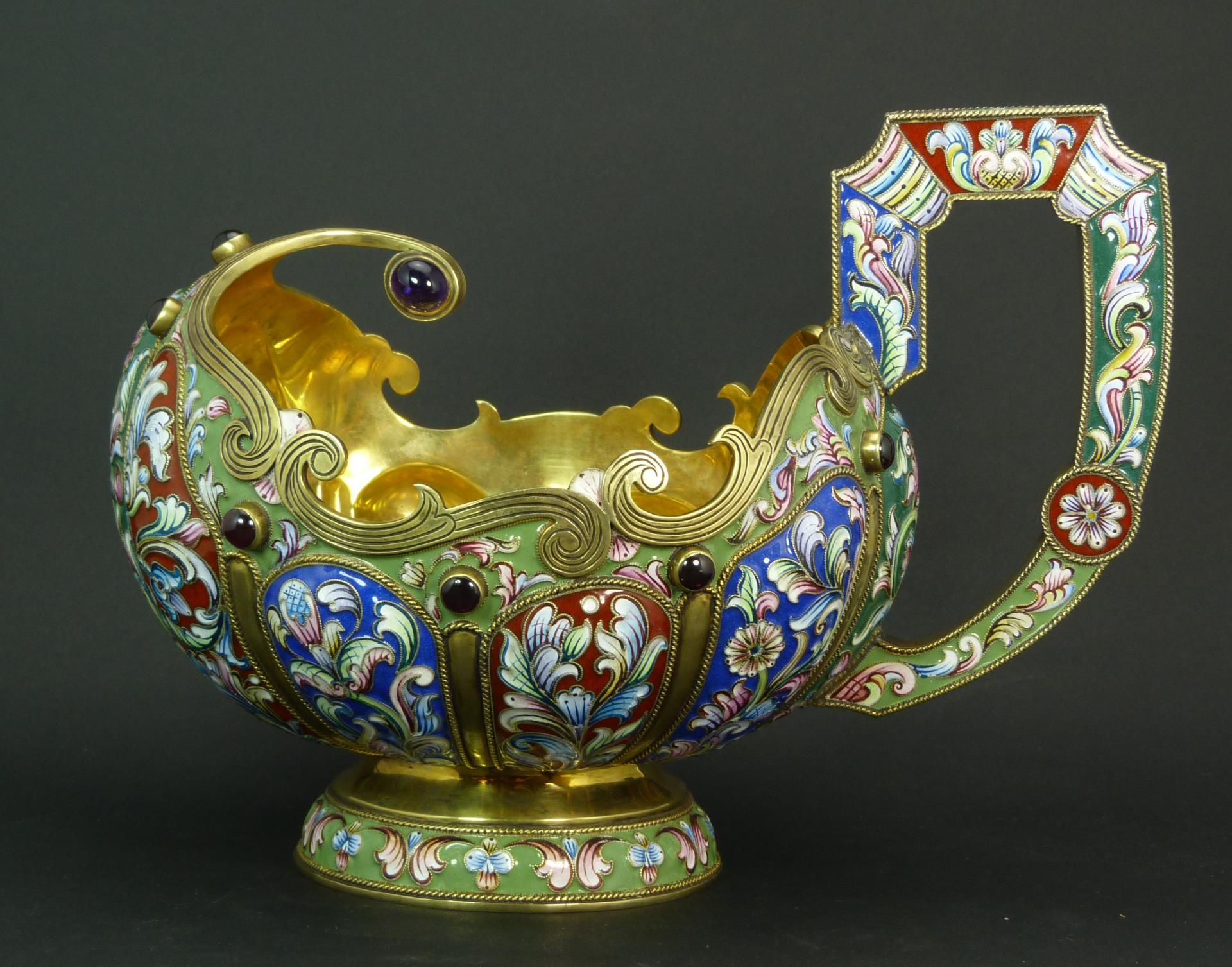 A large and interesting Russian enameled silver Kvosh. Jeweled throughout with 13 round cabochon rubies. Vibrant multicolor scrolled floral designs over red, green and blue grounds. Gold wash throughout. Bottom holds impressed 88 silver marks with town marks. Also holds Faberge Cyrillic town marks.