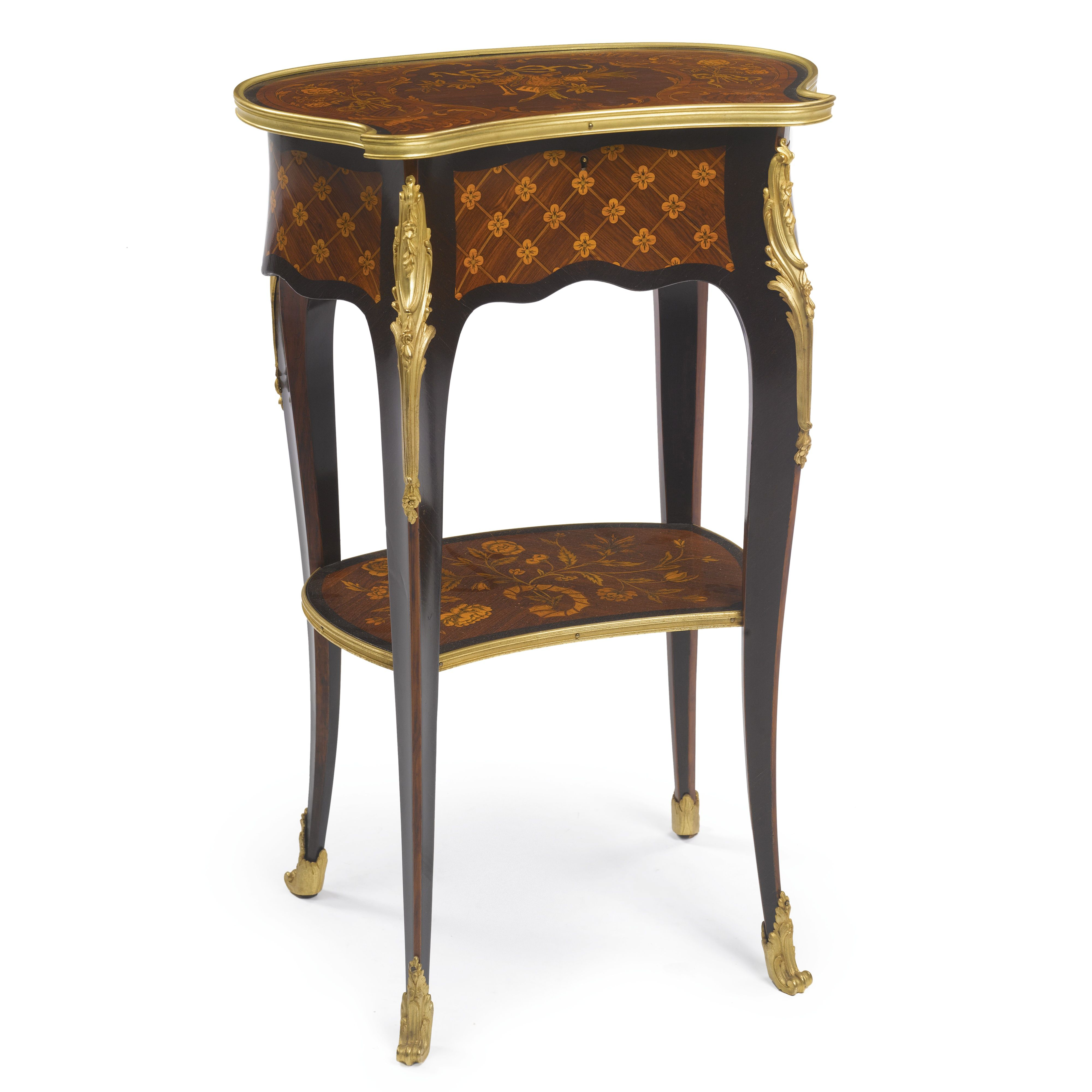 A LOUIS XV STYLE GILT-BRONZE MOUNTED PURPLEWOOD, KINGWOOD AND SATINWOOD FLOWER-HEAD TRELLIS PARQUETRY AND VARIEGATED FRUITWOOD FLORAL AND FOLIATE MARQUETRY WORKING TABLE PARIS, CIRCA 1900 the kidney shaped hinged top centered by a musical trophy with a bagpipe within a foliate cartouche, opening to a satinwood interior with three divided compartments, the frieze with a deep drawer to the righthand side height 29 1/4 in.; width 20 in.; depth 13 in. 74.5 cm; 51 cm; 33 cm