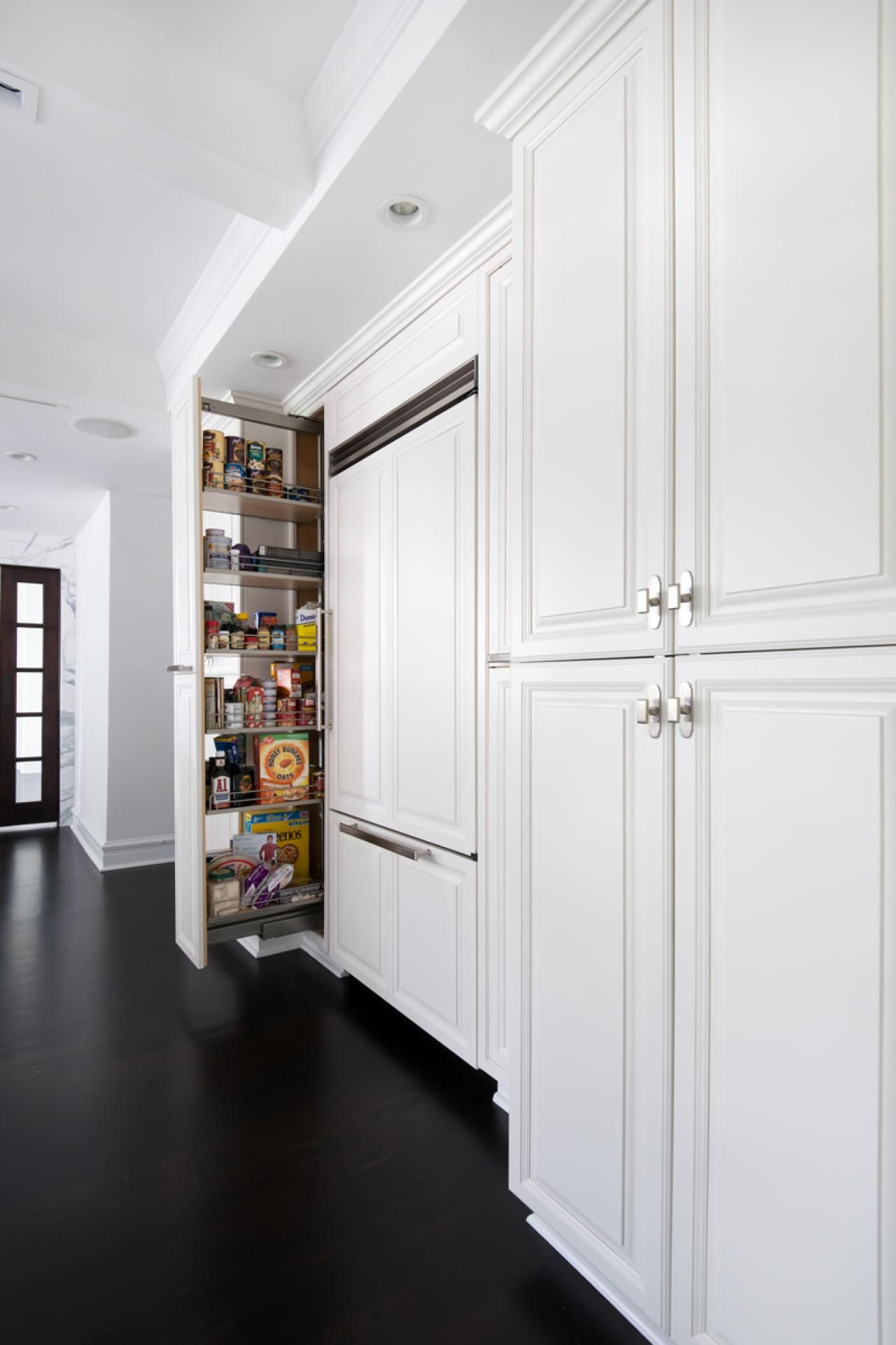 An allwhite kitchen with floortoceiling cabinets creates a light