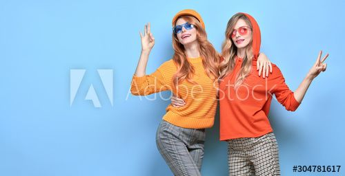 Two Lovable embracing fashionable woman sisters in Trendy orange yellow outfit. Carefree beautiful funny stylish friends smiling shows peace sign on blue. Happy fashion girl, colorful positive banner , #AFFILIATE, #outfit, #yellow, #orange, #funny, #beautiful #Ad