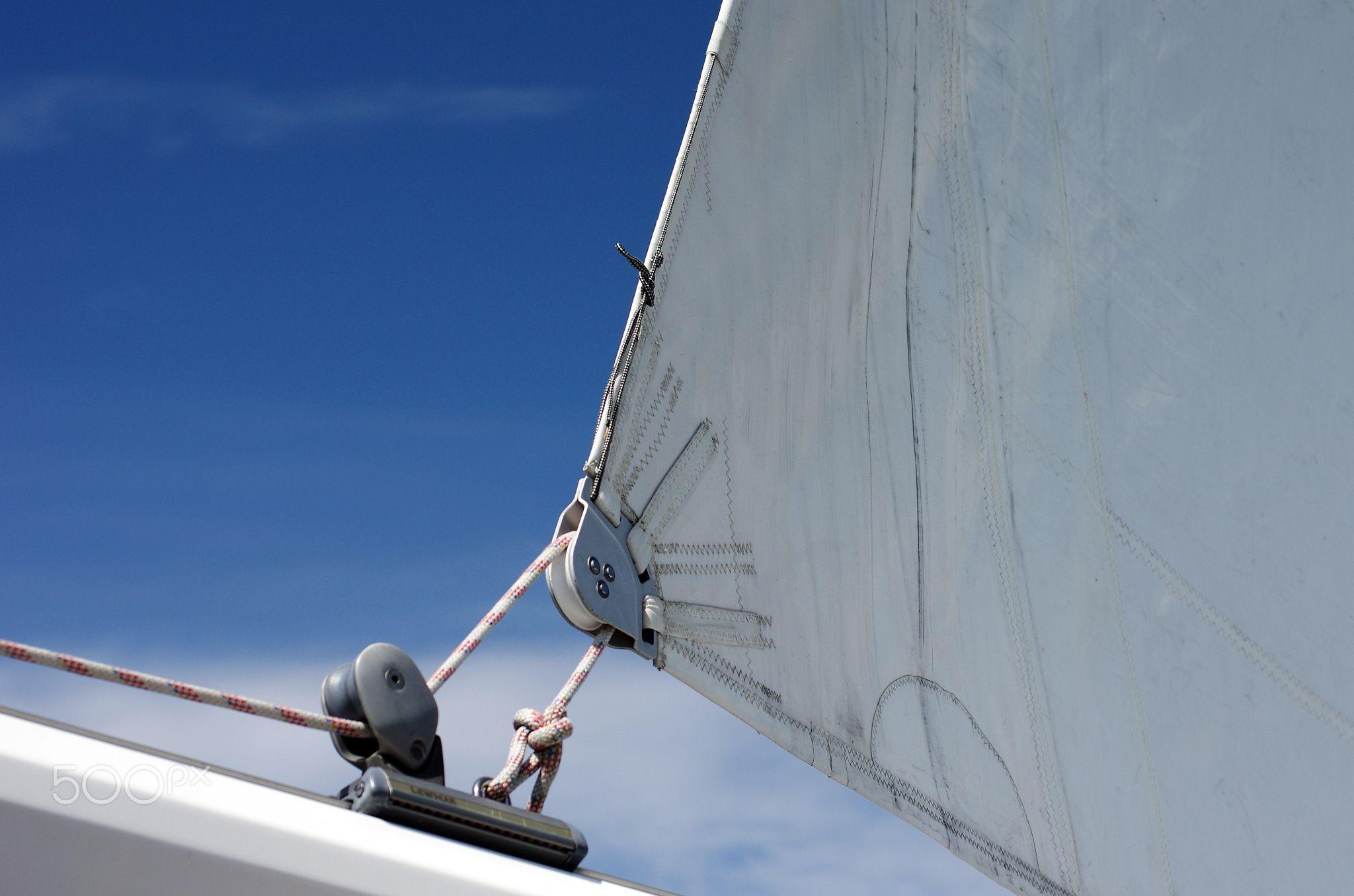 Segel - Detailfotografie vom Segeln. Detail Photography from sailing.  Segeln ist die Fortbewegung eines Segelschiffs oder eines Segelboots unter Nutzung der Windenergie. Segelschiffe hatten über viele Jahrhunderte weltweit eine große Bedeutung für Handel und Transport, Kriegsführung und Fischfang. Gegen Ende des 19. Jahrhunderts begann ihre Verdrängung durch maschinengetriebene Schiffe, die von den Bedingungen des Wetters weniger abhängig waren und kürzere Fahrtzeiten, geringeres Personal…