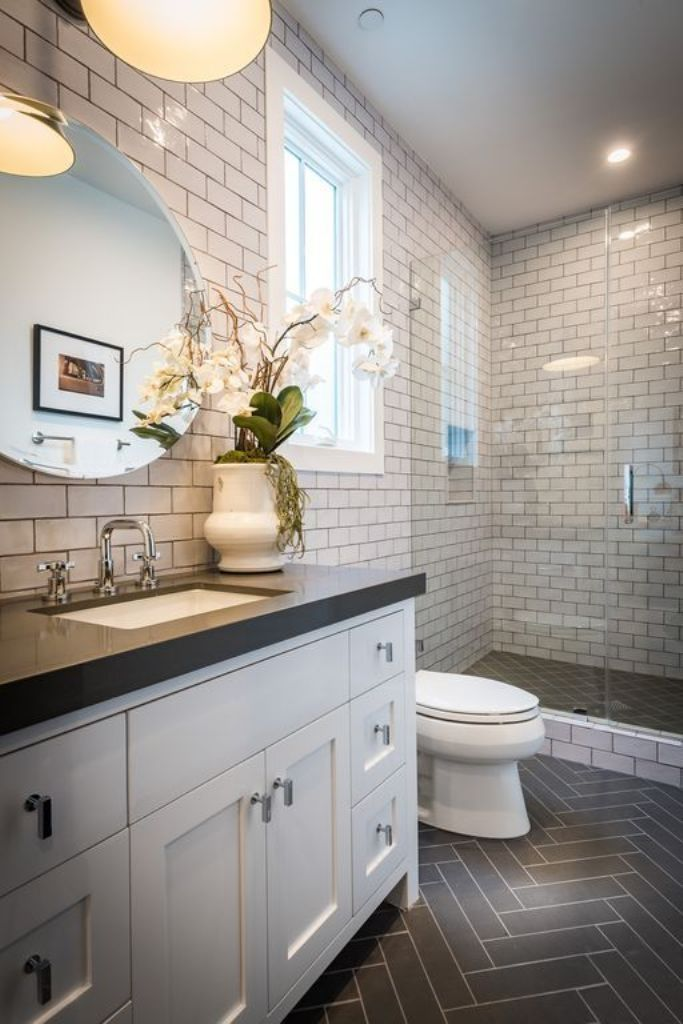 Brown Herringbone Tile Floors With White Vanity Cabinet Using Chrome Hardware With Round Shaped Mirror Small Bathroom Tiles Bathroom Tile Designs Tile Remodel