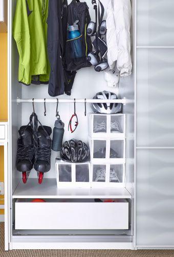 Det indvendige af et garderobeskab. Der hænger rulleskøjter i en krog på en stang. Sko i IKEA opbevaringsbokse.